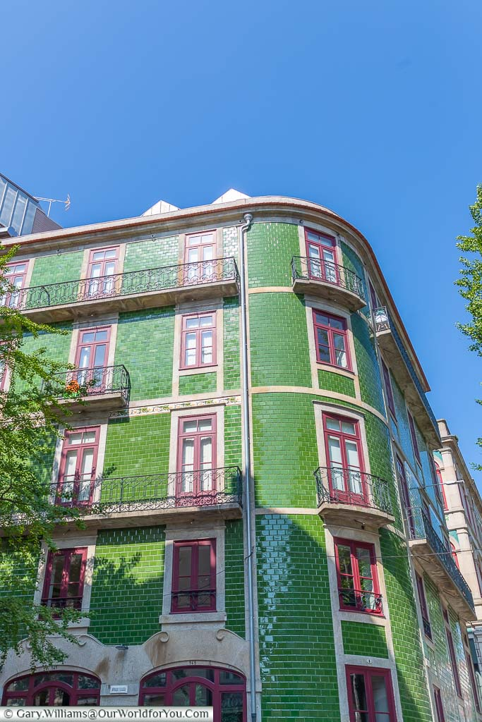 A beautiful green tilled apartment block, with crimson framed windows in Porto, Portugal