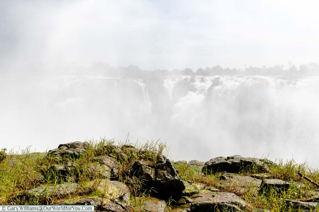 The view of the Zambezi River flowing into the gorge through the mist generated from Victoria Falls during the high water season