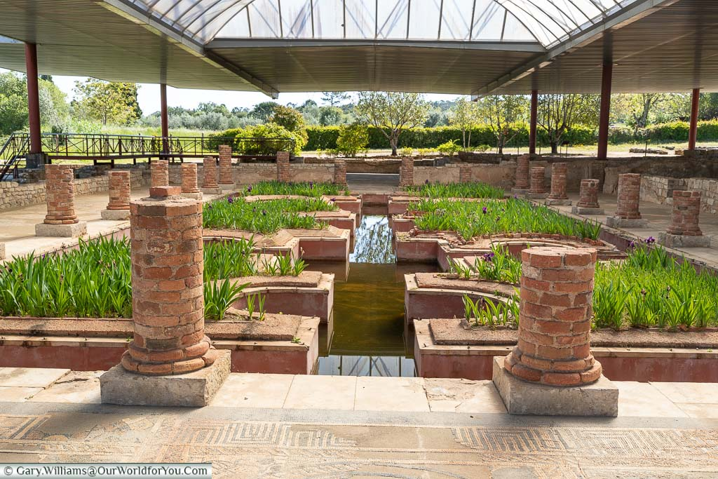The restored water gardens at the Roman ruins of Conímbriga under a protective roof.