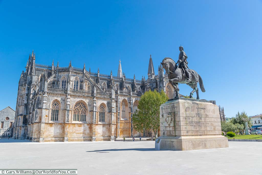 An equine statue of a Portugues hero in front of the gothic Monastery of Batalha