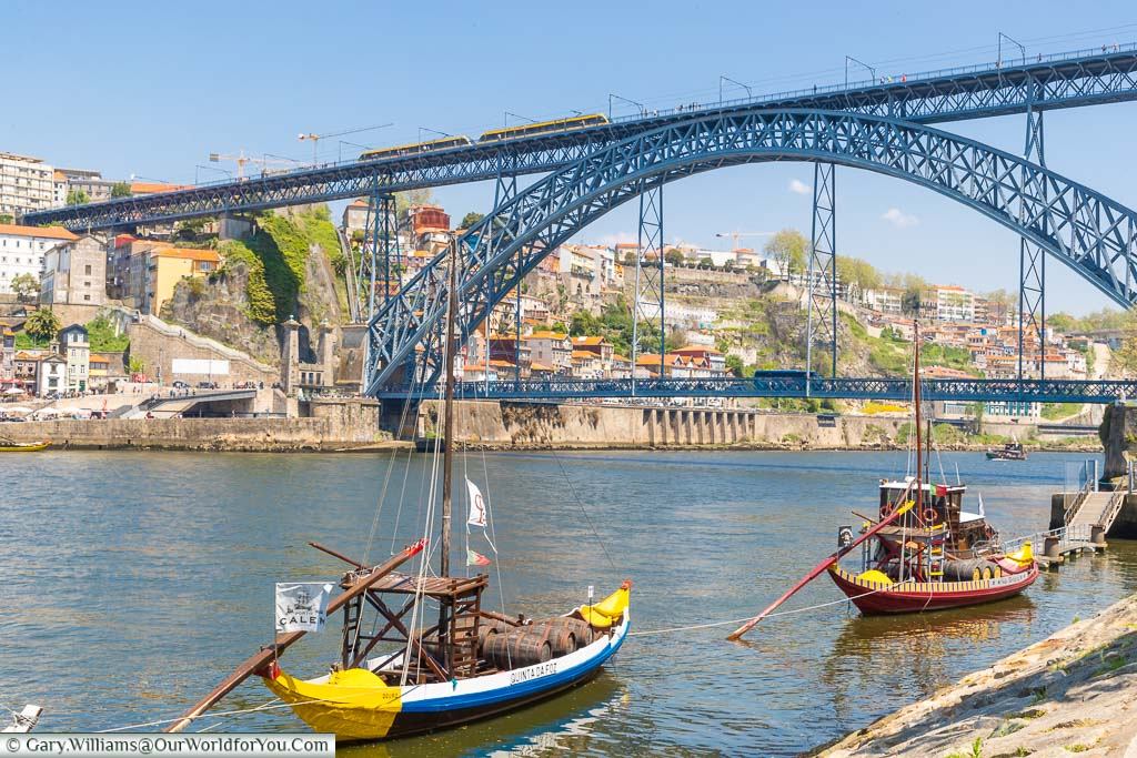 The small traditional Rabelo sailing boats moored up in front of the Ponte Luís I bridge over the River Douro in Porto, Portugal