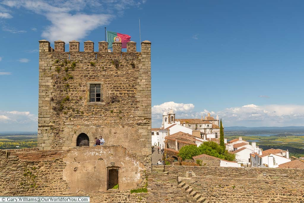 The view from the castle walls of Monsaraz, in Portugal, past the gate tower to the town's white houses beyond.