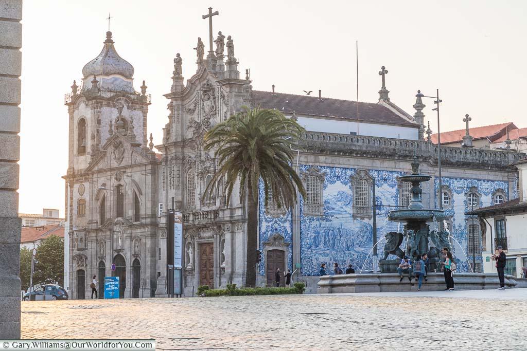 A few poeple gathering around the Fonte dos Leões in front of the blue tiled Igreja do Carmo and Igreja dos Carmelitas in Porto, Portugal