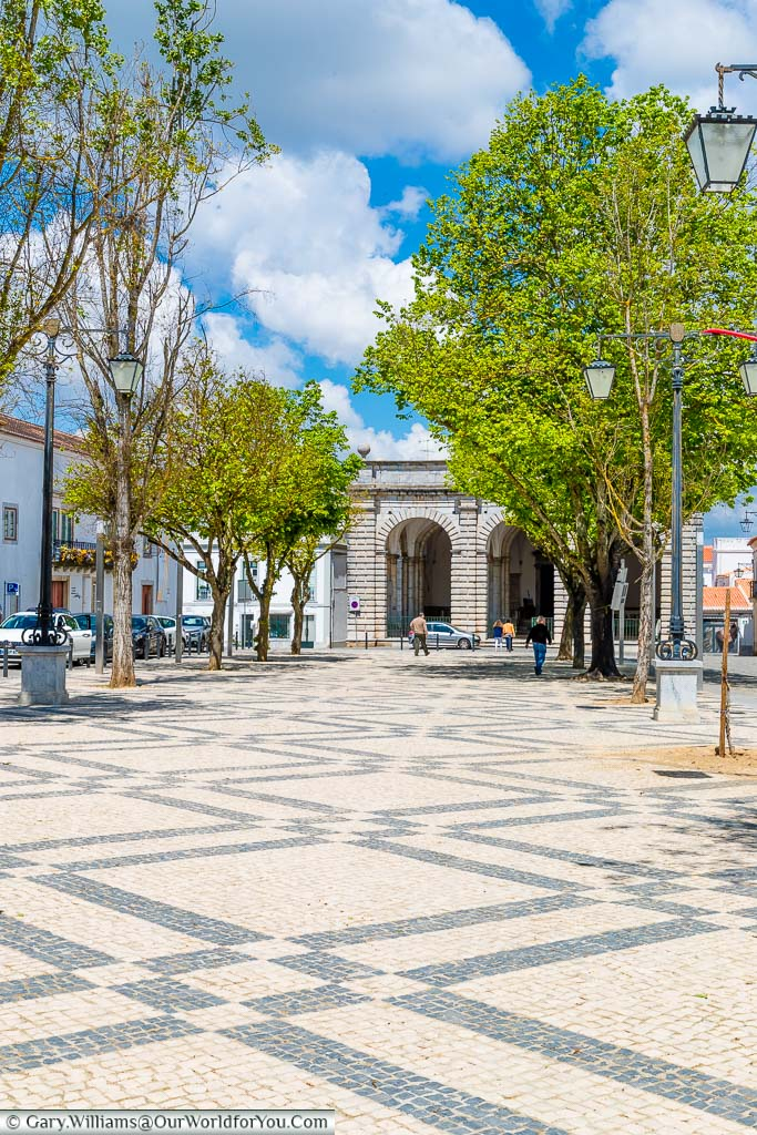 The tree lined, tiled, Praça da Republica in Beja with the porch to the Igreja da Misericórdia de Beja visible at then end of the square.