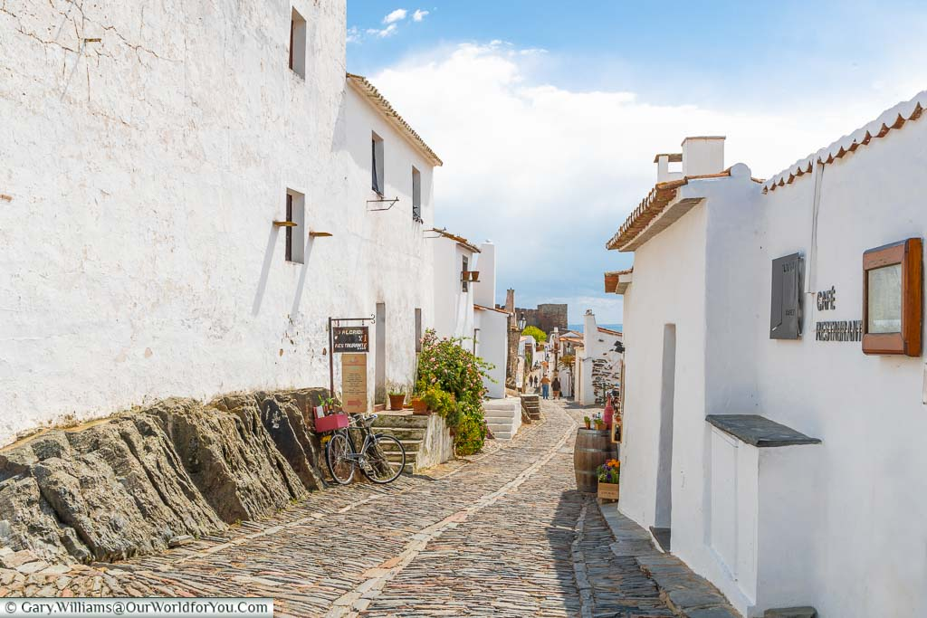 A narrow cobbled lane between the white buildings of the historic hilltop town of Monsaraz in Portugal