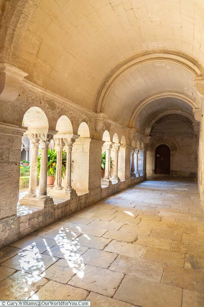 The cream stoned collonaded cloister of the Monastery of Saint-Paul de Mausole with views onto the garden beyond
