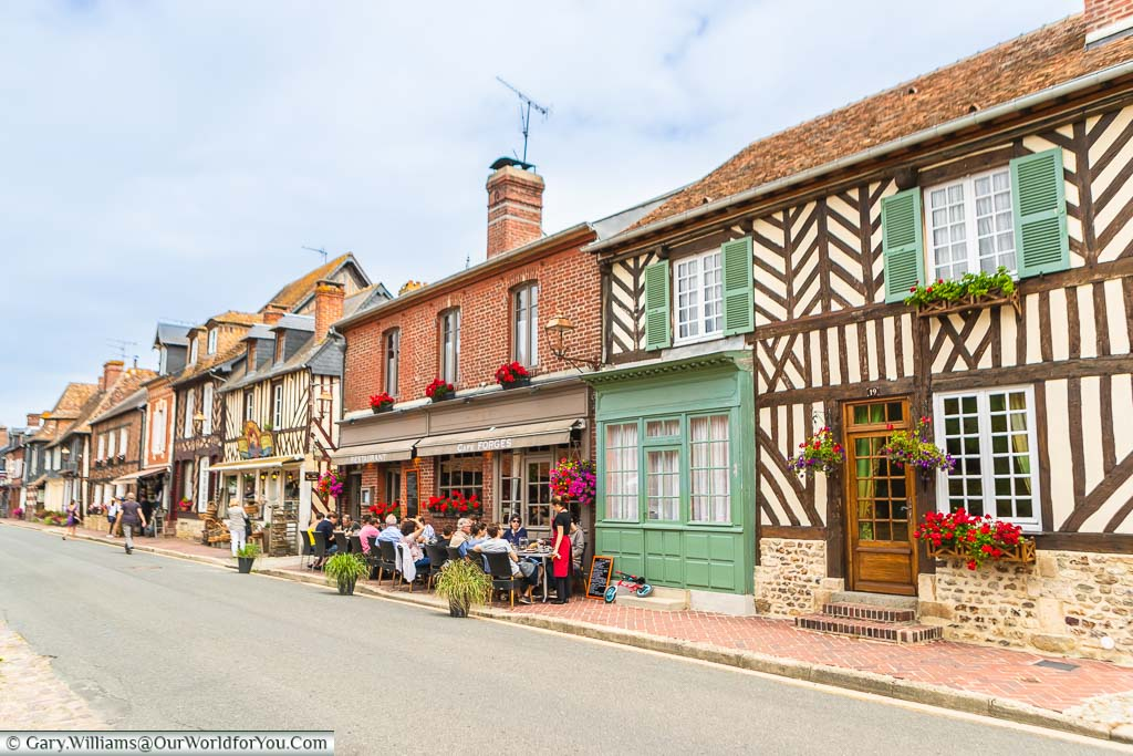 The high street in Beuvron-en-Auge with half-timbered homes, shuttered windows and tables & chairs outside a café