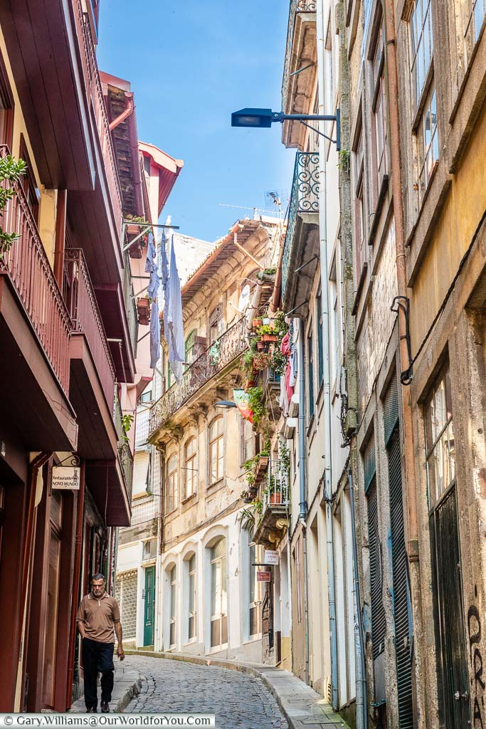 A gentleman strolling down a steep, narrow, cobbled lane, in the centre of Porto