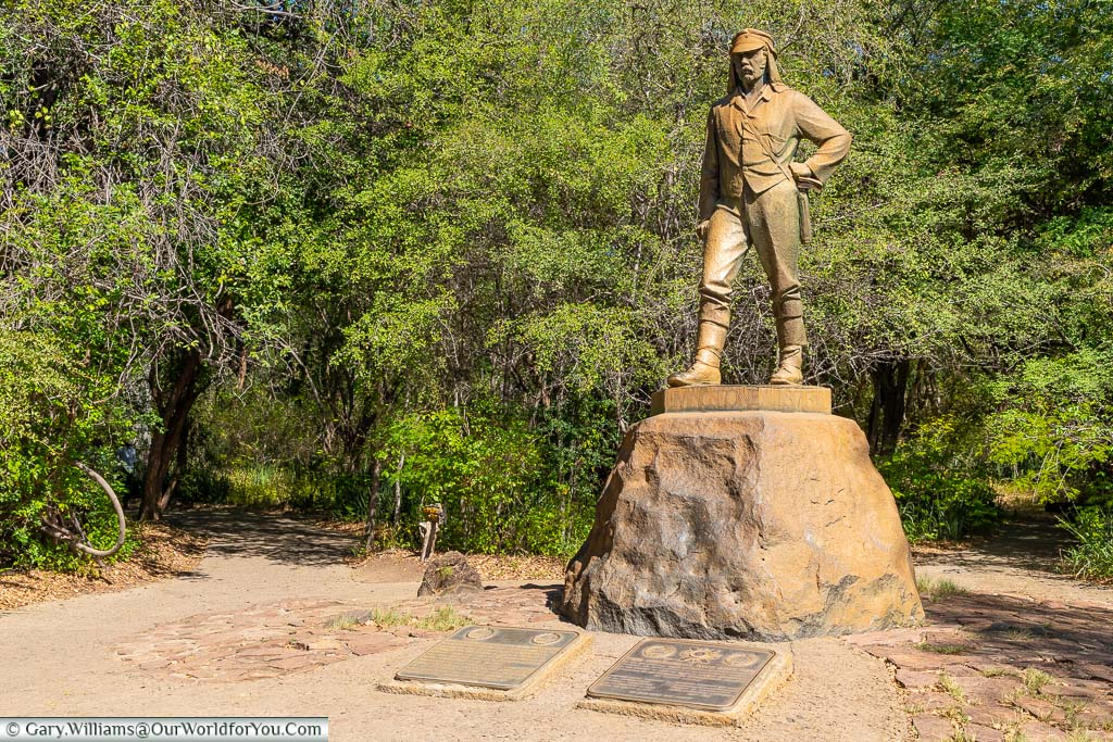 A larger than life statue to David Livingstone, in his 19th-century attire, on a rock plinth in the Victoria Falls visitor park.