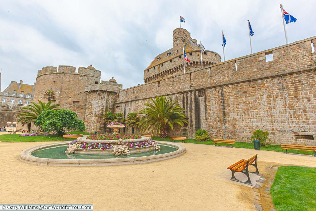 A public garden, featuring a stone fountain, planted out with bright flowers in front of the city walls of Saint-Malo, Brittany, France