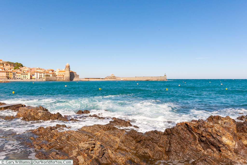 A view across the bay to the Collioure Lighthouse from the rocky shoreline in the southeast of France