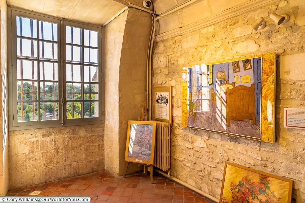 A small stone room in the Monastery of Saint-Paul de Mausole displaying prints of Van Gogh's working, including a work depicting a room at his sanctuary.