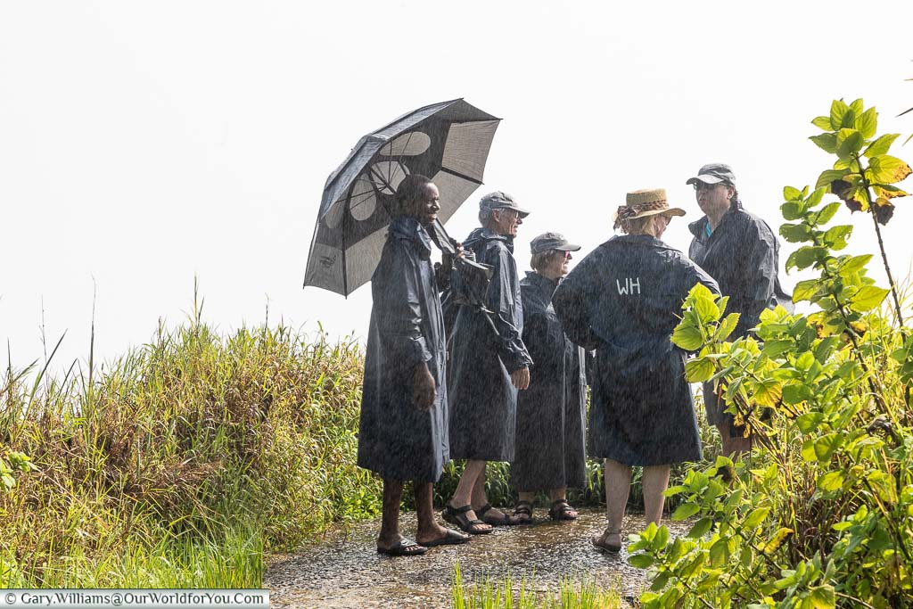 A group at a Victoria Falls viewpoint wrapped up in waterproof Ponchos against a heavy white mist.