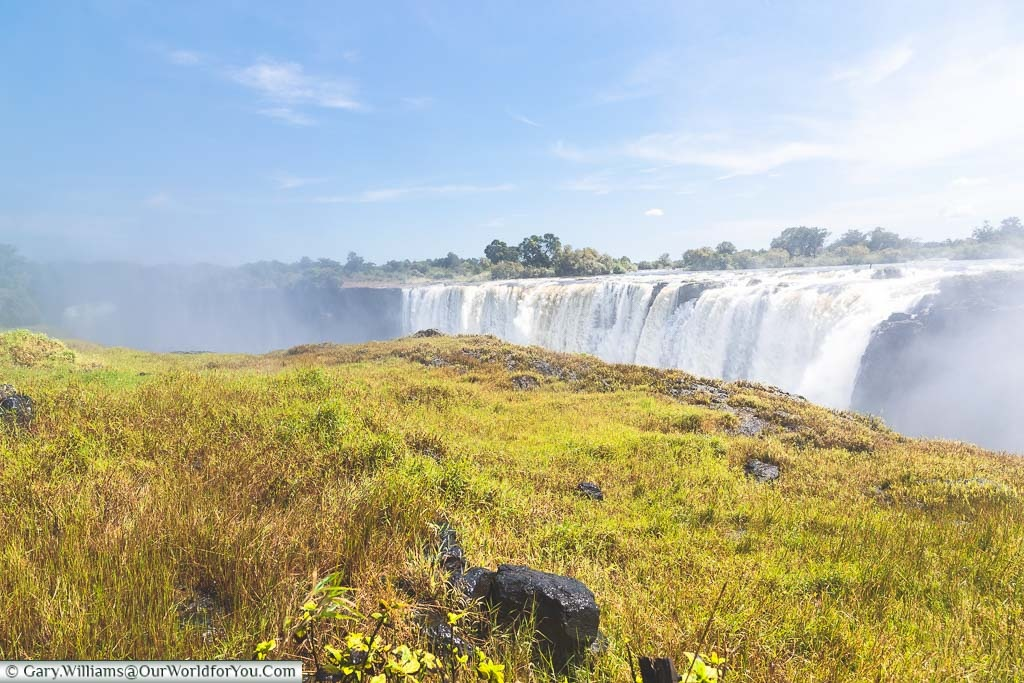 The lush green grass in front of the gorge and Victoria Falls from the Zimbabwe side