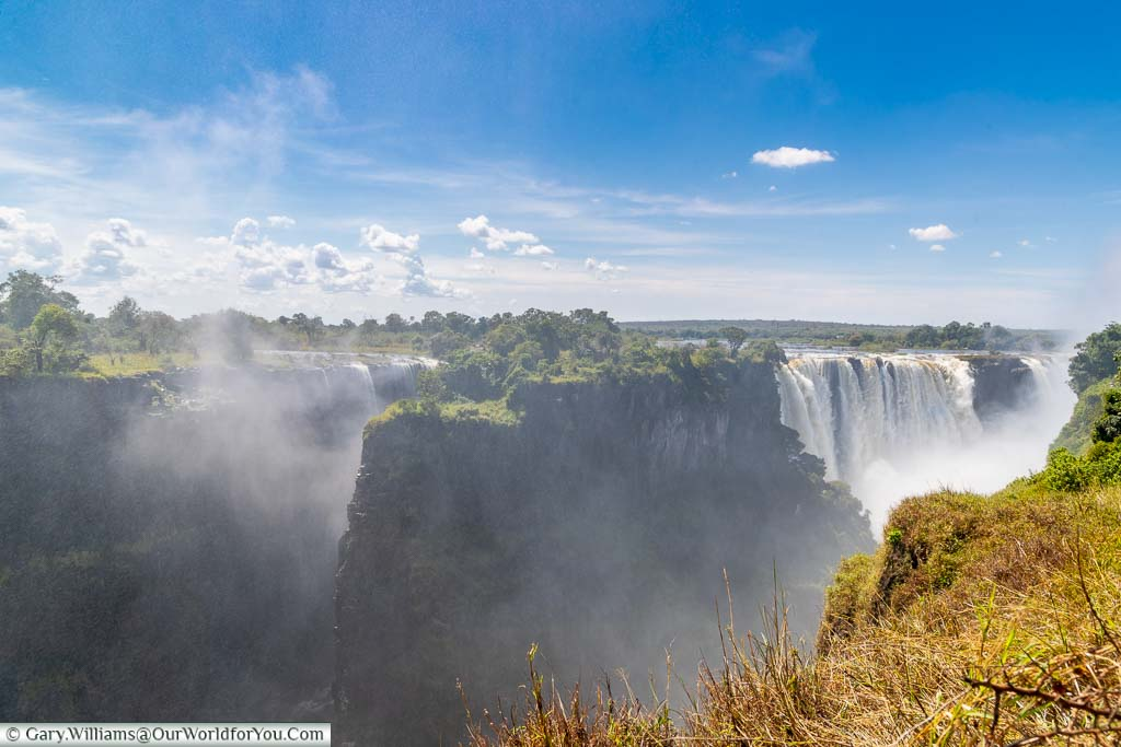 A view of Livingstone Island sits in the flow of the Zambezi between the Victoria Falls. Behind the island, the main falls cascades over the edge underneath the deep blue Sky