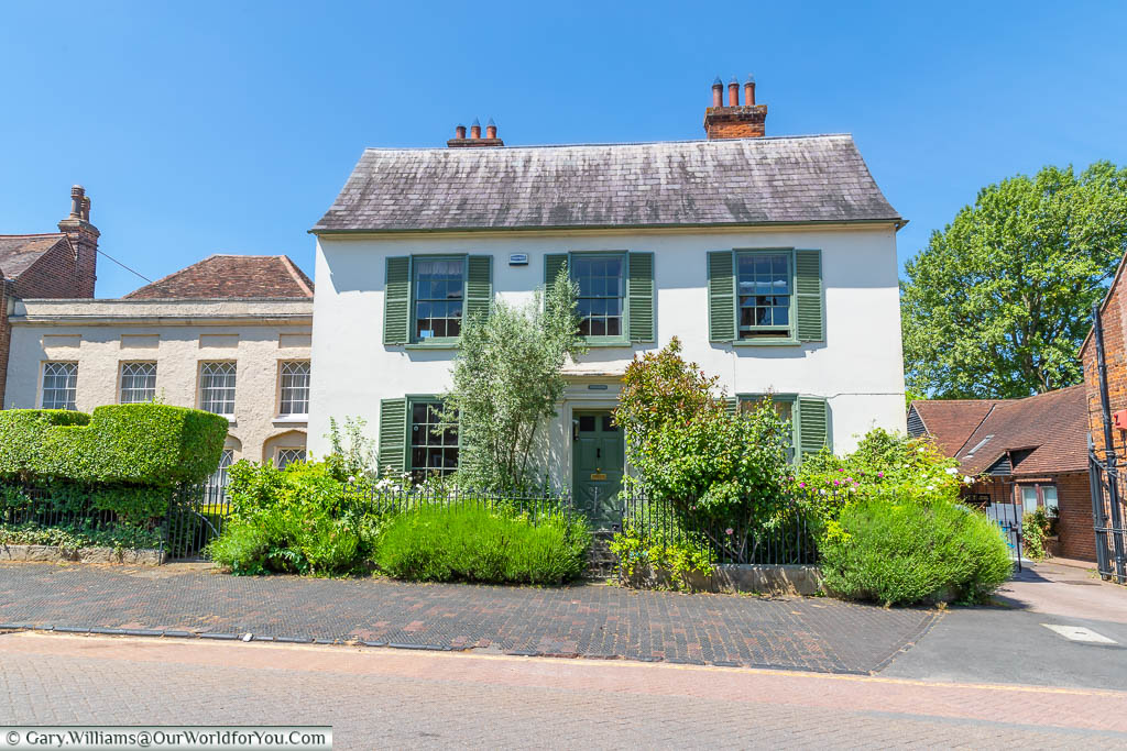 A white beautiful detached home with green shuttered windows on West Malling High Street