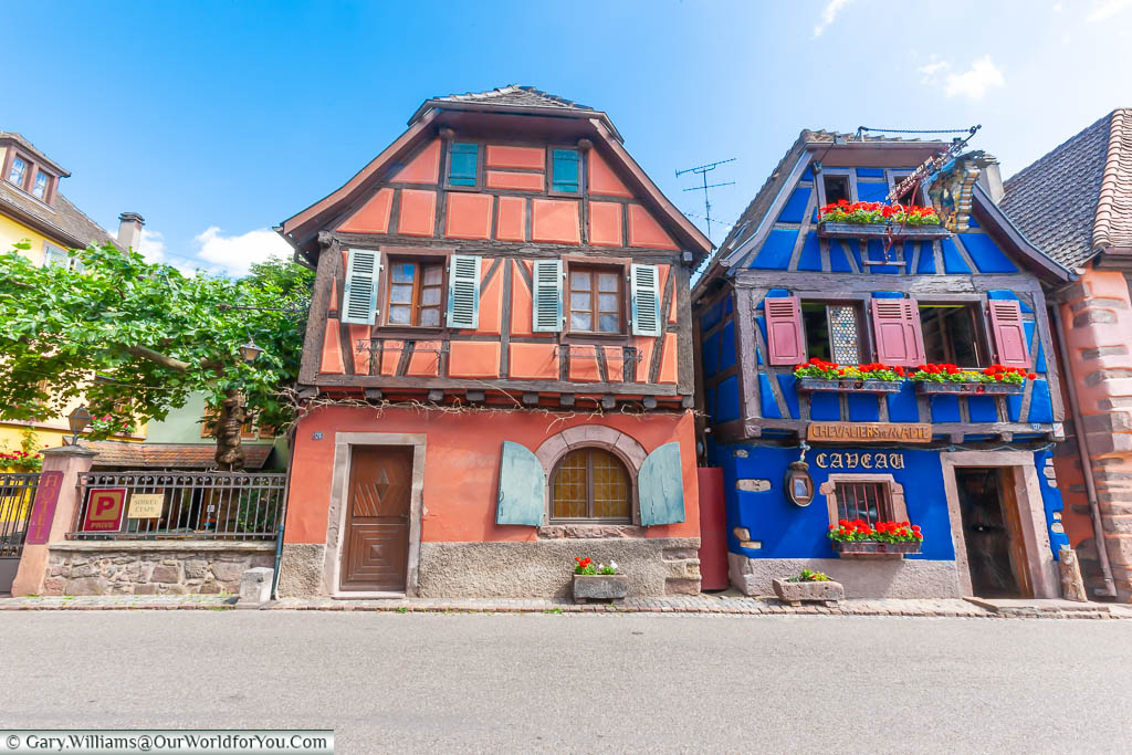 Two brightly painted, half-timbered and shuttered building in the Alsace village of Niedermorschwihr, France