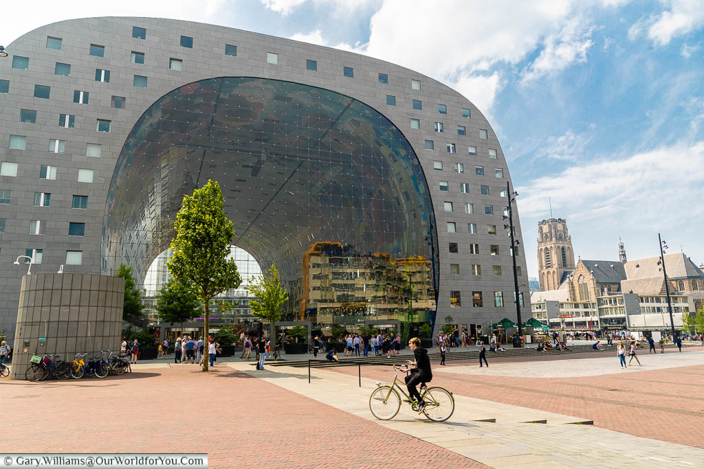 A cyclist riding in front of the modernist Markethall in Rotterdam