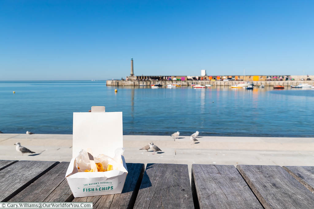 A small portion of Fish 'n' Chips in a cardboard container by the sea at Margate, Kent