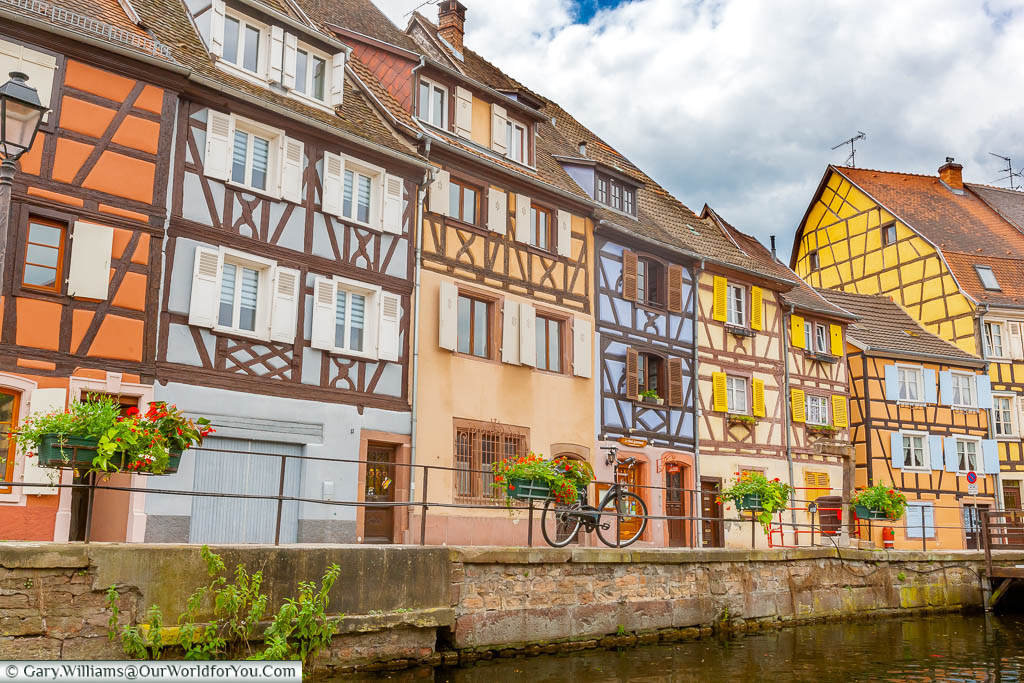 A bike resting against railings at the canal's edge in front of colourful half-timber buildings in 'La Petite Venice', Colmar, France
