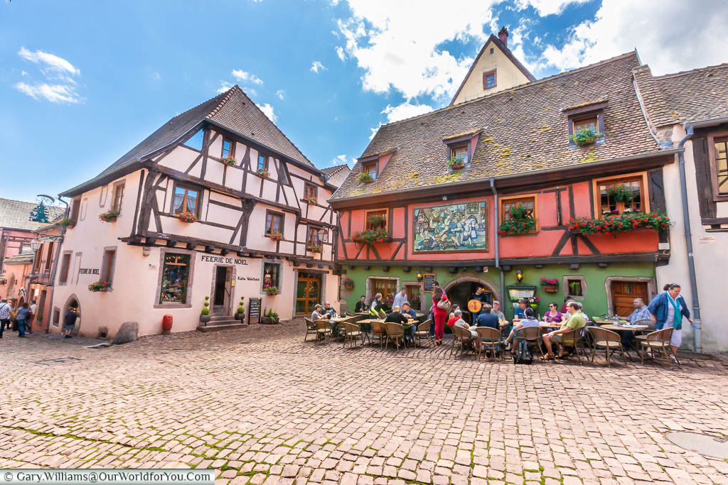 A traditional half-timbered bar & restaurant with tables & chairs spread out into the cobbled square outside in the French town of Riquewihr, on the Alsace Wine Route