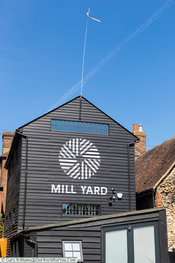 A white-painted sign & logo for Mill Yard on the side of a black weatherboarded grain tower in West Malling, Kent