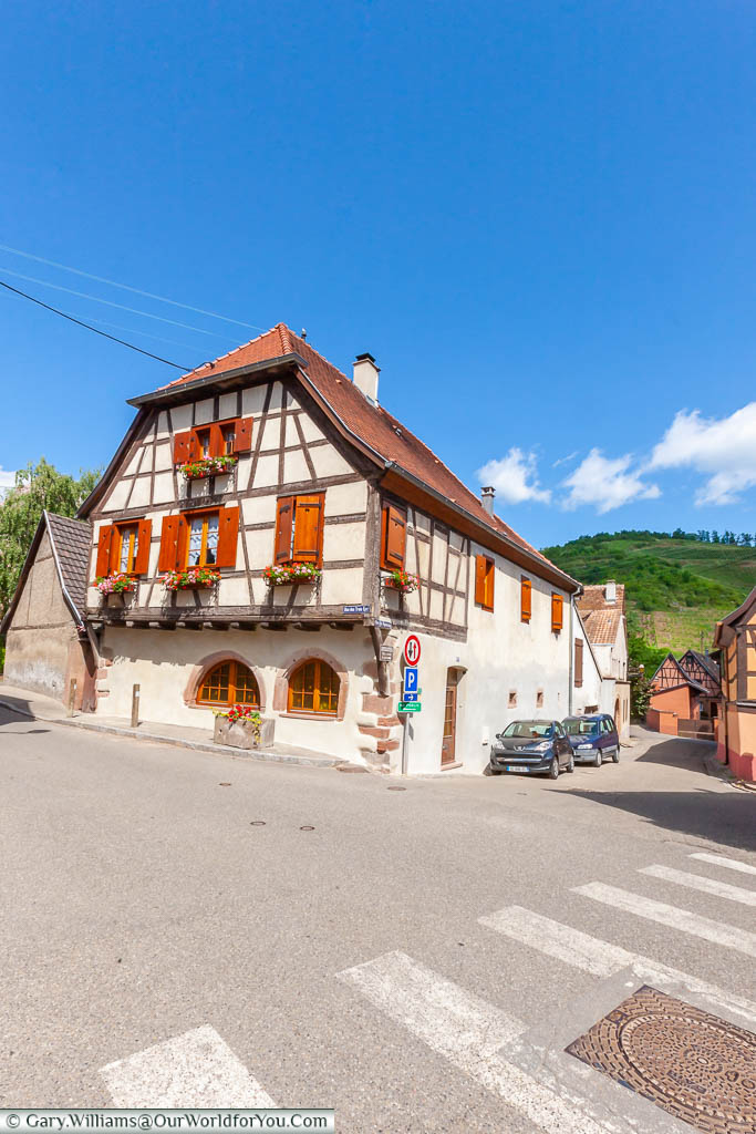 A half-timbered and shuttered building in front of the vineyards on the hillside behind in Niedermorschwihr , France
