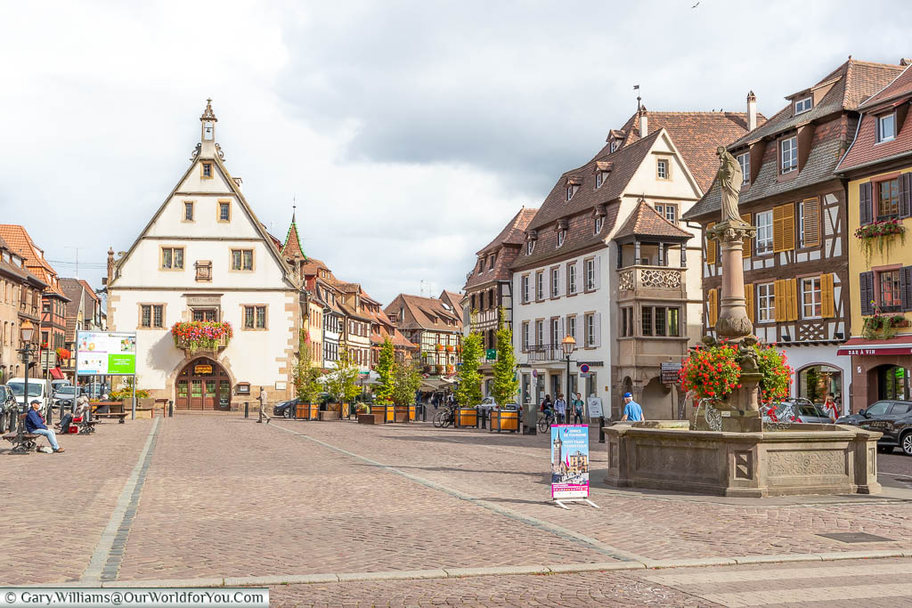 A stone fountain in the town square in Obernai, in the Alsace region of France, lined on all sides by historic half-timbered buildings of the region