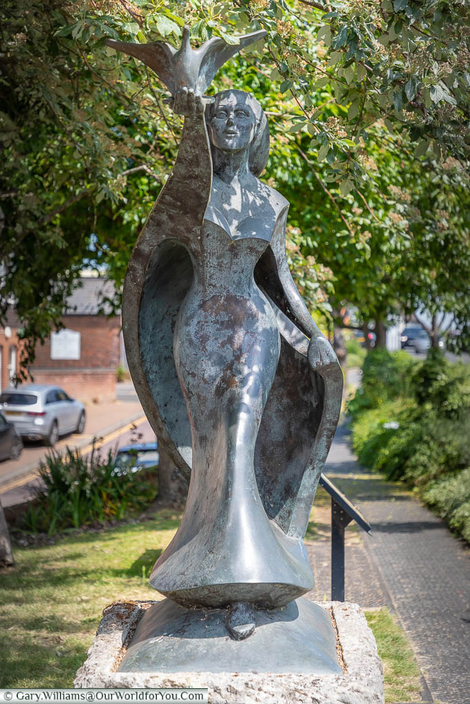 The front view of the modern bronze 'Hope' sculpture depicting a woman stepping forward, releasing a dove of peace, on a green next to West Malling High Street