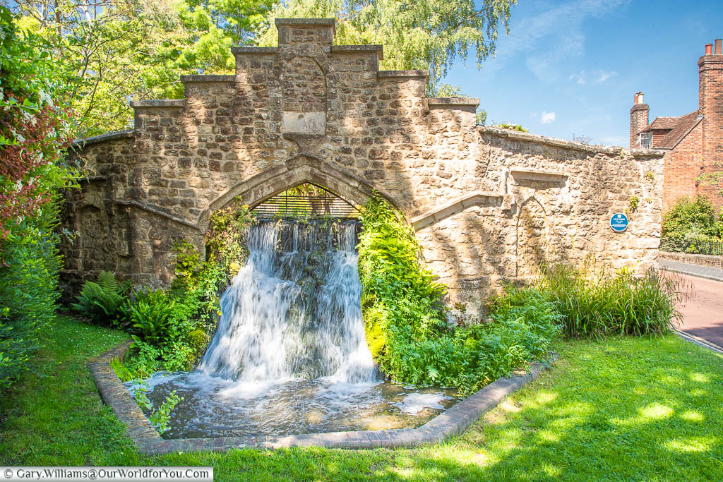 Water cascading down a 1.5-metre man-made waterfall through a medieval stone arch at the rear of St Mary's Abbey in West Malling Kent