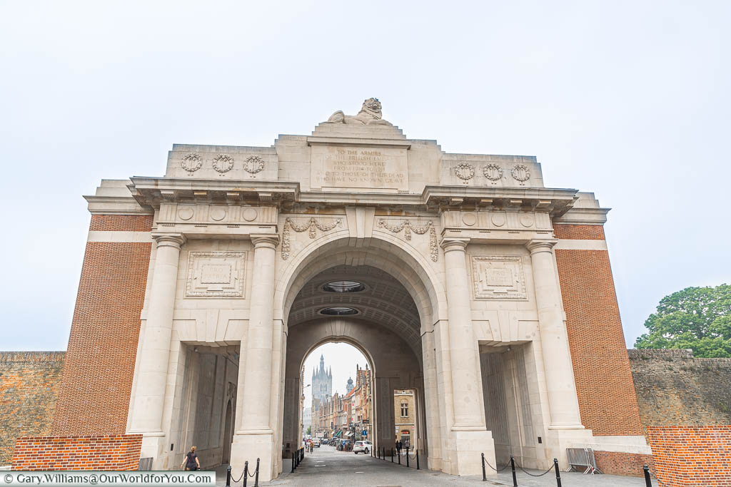 Looking through the red brick & cream stone archway of the Menin Gate in Ypres to the bell tower of the Cloth Hall in the distance