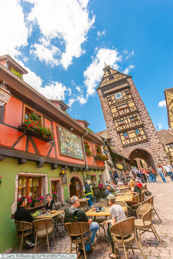 A people sitting outside a traditional half-timbered bar & restaurant in front of one of the city gatehouses, incorporating a clocktower, in Riquewihr France on the Alsace Wine Route