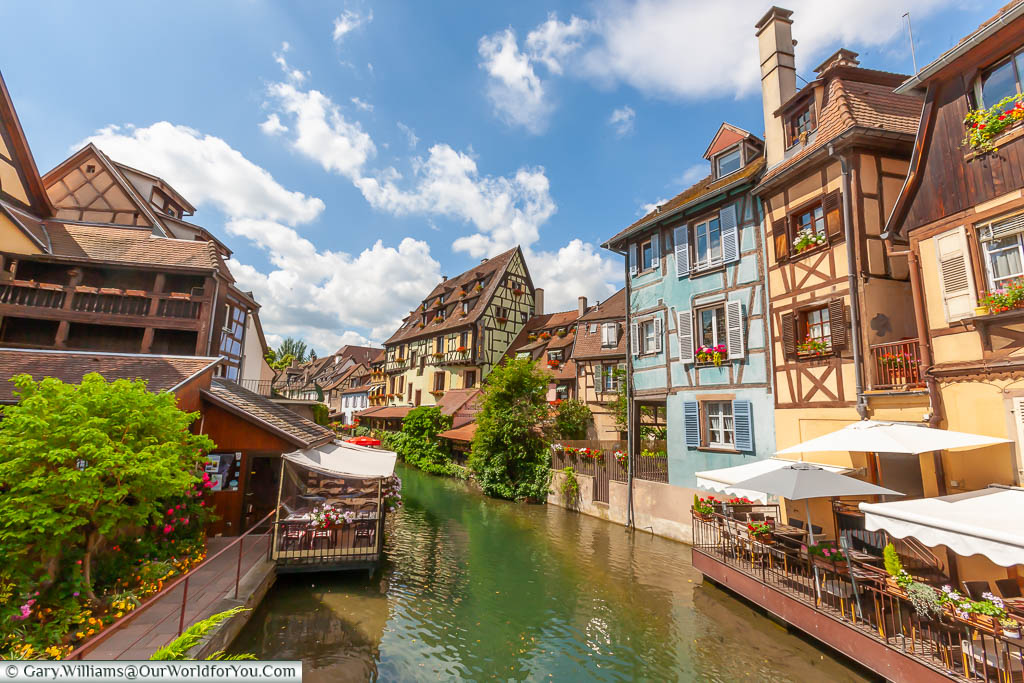 Restaurants at the base of brightly coloured, half-timbered buildings lining the canal in Colmar, France