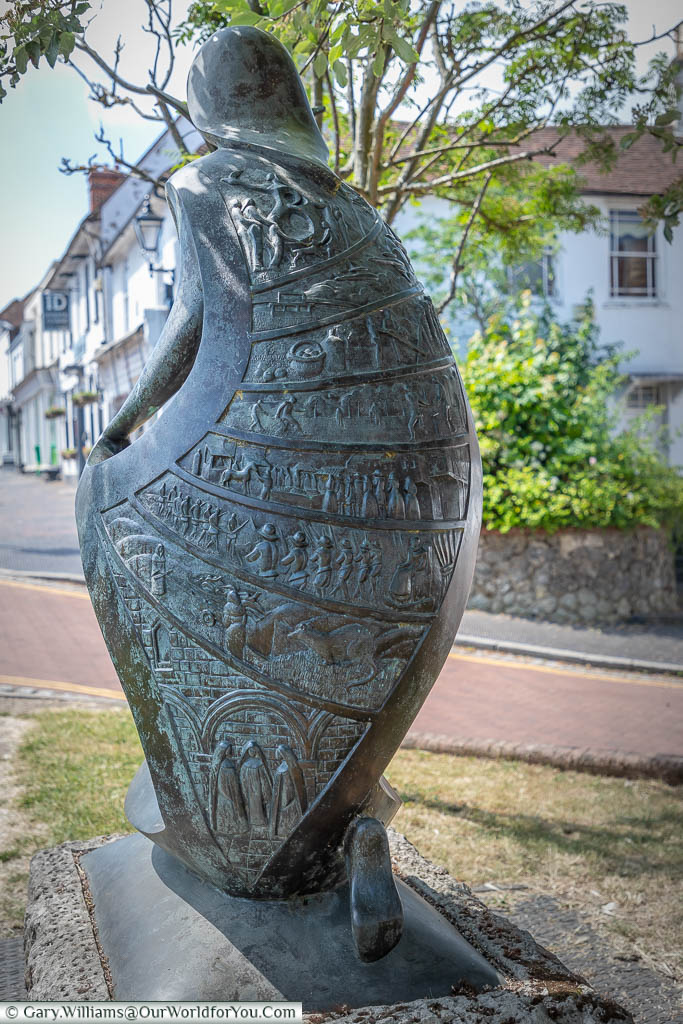 The rear of the 'Hope' sculpture where the cloak covering the statue is inlaid with 8 panels depicting scene throughout West Malling's history