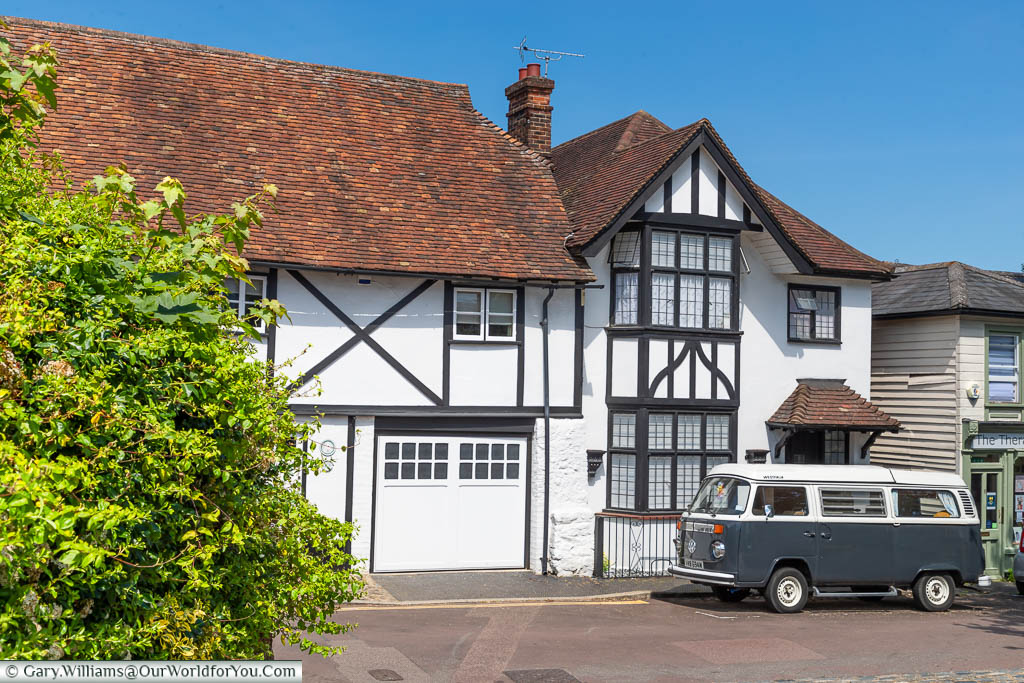 A VW Camper van in front of a Tudor period timber-framed home in King Street, West Malling, Kent