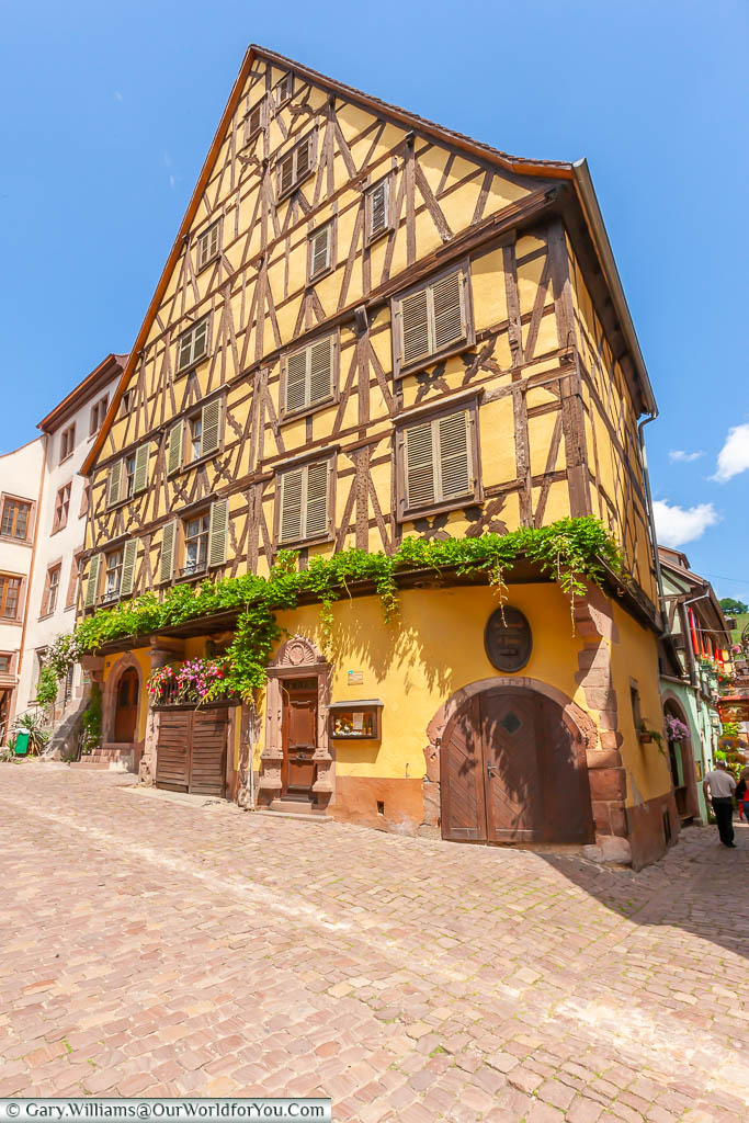 A traditional half-timbered building on the corner of two cobbled lanes in Riquewihr, France