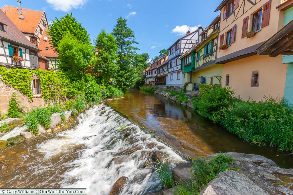 Water flowing across a stone weir between traditional brightly coloured Alsace half-timbered buildings in Kaysersberg, France