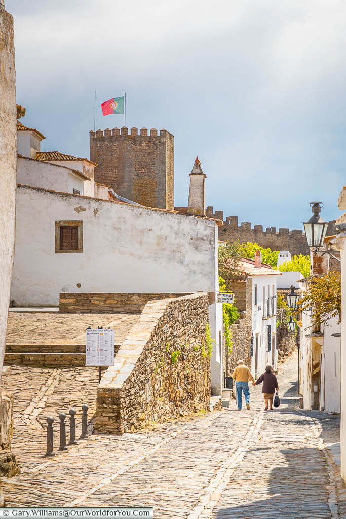 An elderly couple walking along a narrow cobbled lane, with the tower of the town's castle flying the Portuguese flag, in the historic hilltop town of Monsaraz in Portugal