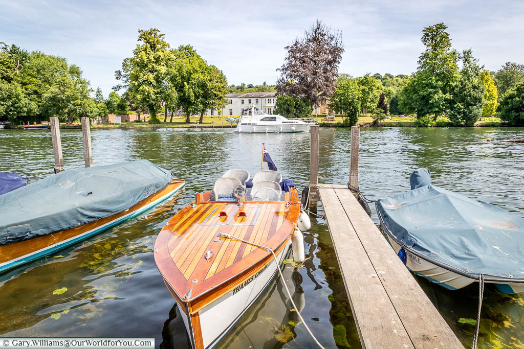 A stylish wooden panelled motor launch moored up on the River Thames opposite the home to the Henley Royal Regatta.