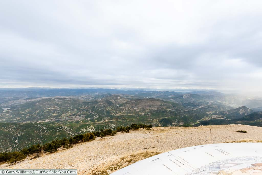A view from the top of Mont Ventoux over the landscape to the north. A plaque points out the mountains in the range in front.
