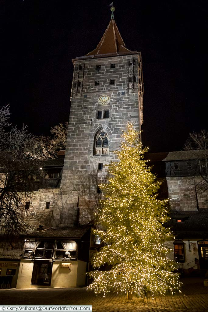 A seven-metre Christmas tree, lit with golden fairy lights, stands in front of a stone tower of Nuremberg's Castle