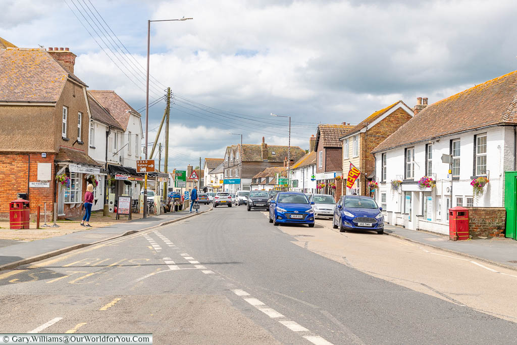 The cars driving through Dymchurch High Street with it's mix of historical buildings