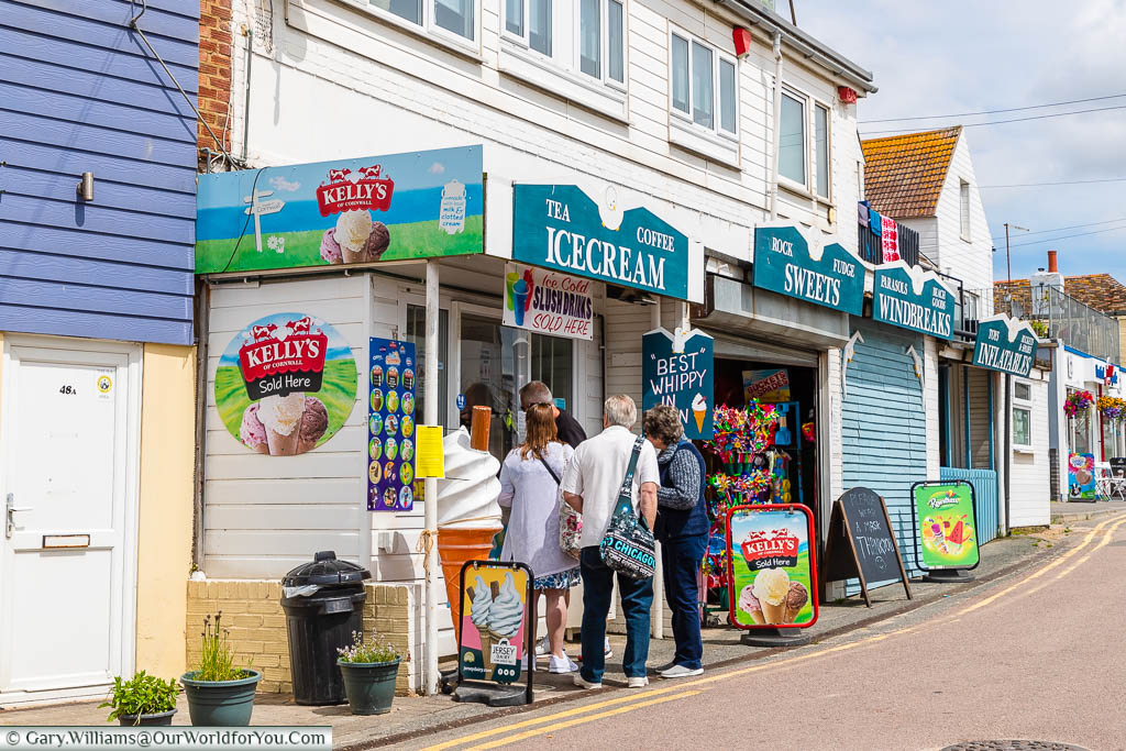 A selection of small shopfronts selling ice-cream, confectionary, gifts and beach items in Dymchurch