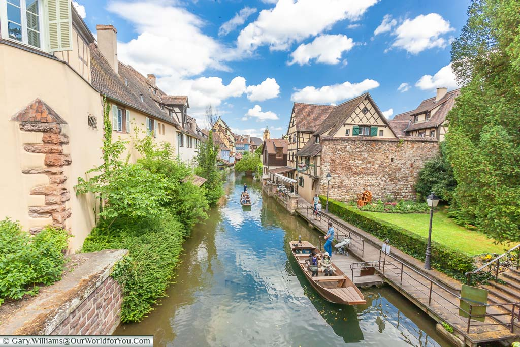 Couples enjoying boat trips on the canals around Colmar in the Alsace region of France on a bright sunny summers day