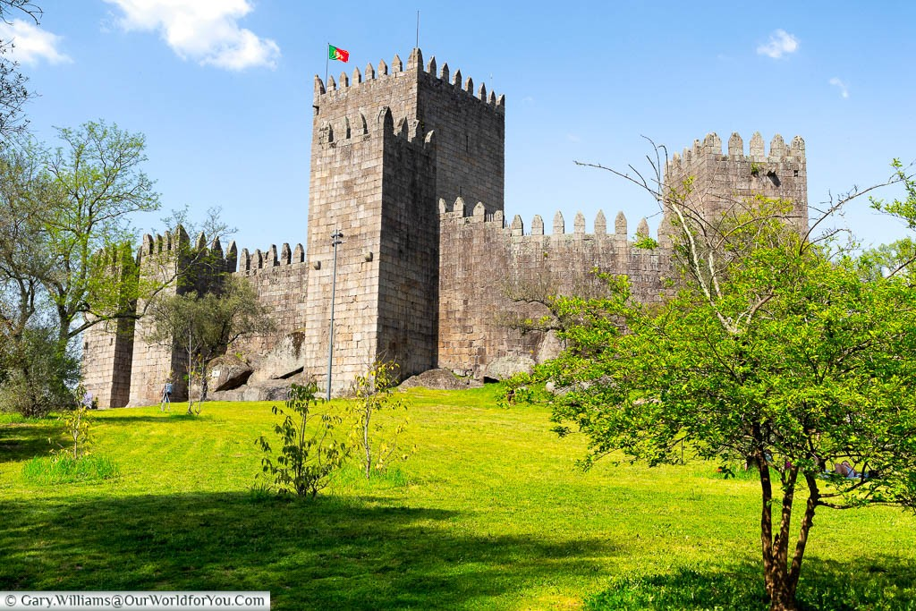 A Portuguese flag flying from a tower of Guimarães Castle behind its defensive walls set on a grassy bank