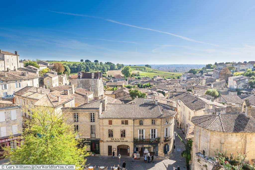 Looking over the stone buildings in the centre of old St-Emillion, with a view to the vineyards of the Bordeaux wine region beyond