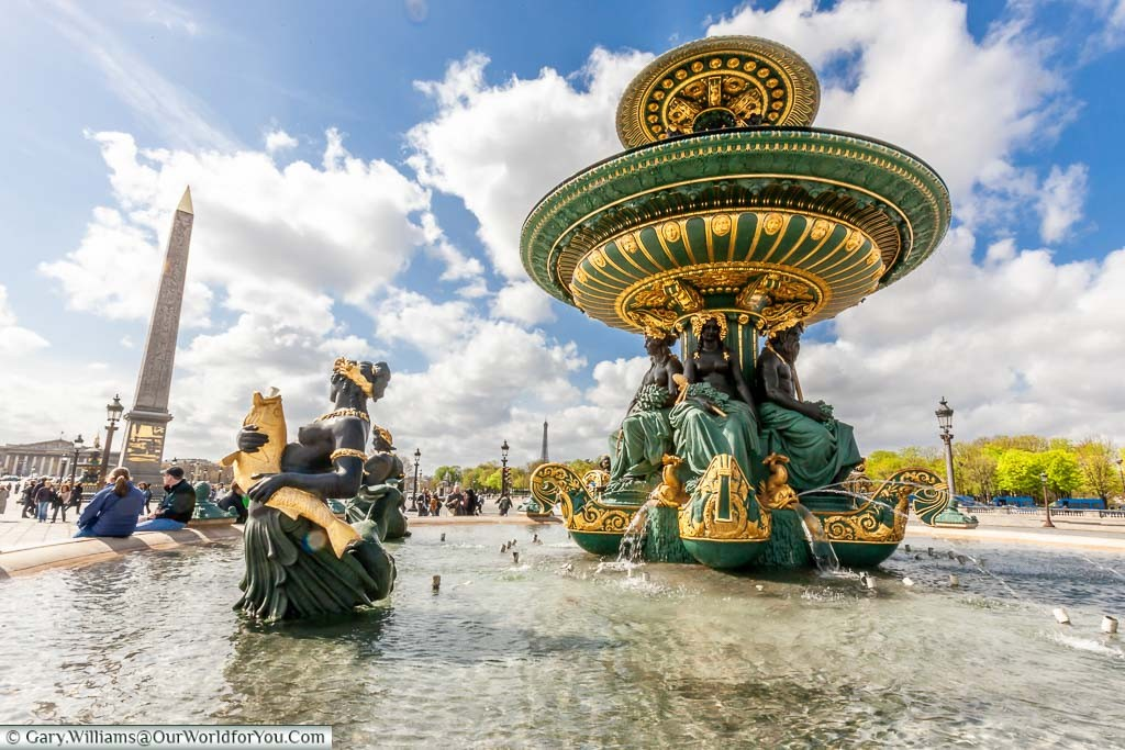 A close up of the Fountain of River Commerce and Navigation in the Place de la Concorde with the Obelisk of Luxor in the background.