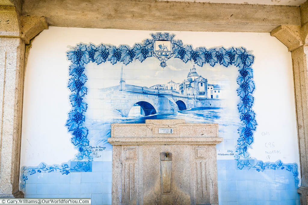 A blue and white tiled image of the Ponte de São Gonçalo in front of the church in Amarante, Portugal
