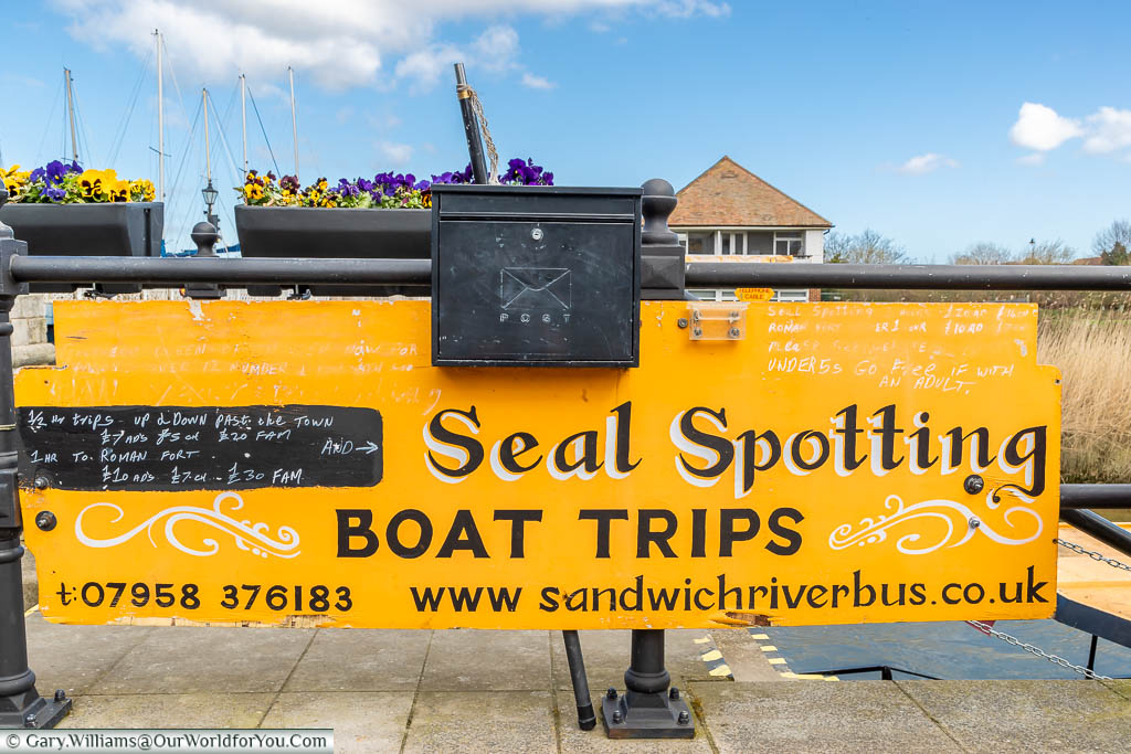 A bright yellow sign offering seal spotting boat trips attached to the railing on the edge of the quayside in Sandwich, Kent
