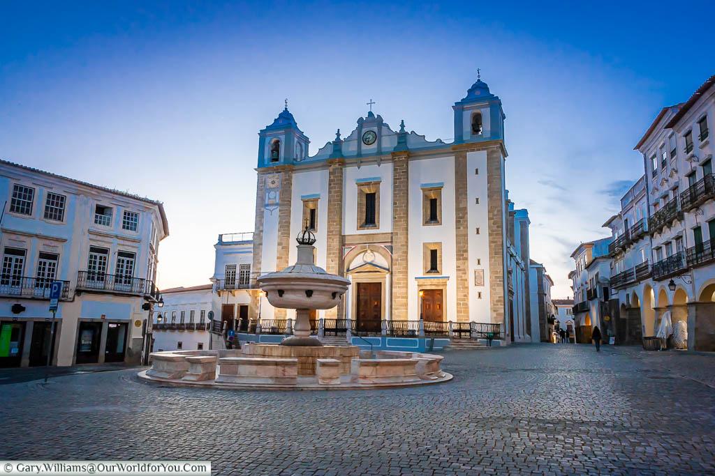 St. Anton's church at one end of the Praça do Giraldo at dusk under a blue sky in Évora, Portugal
